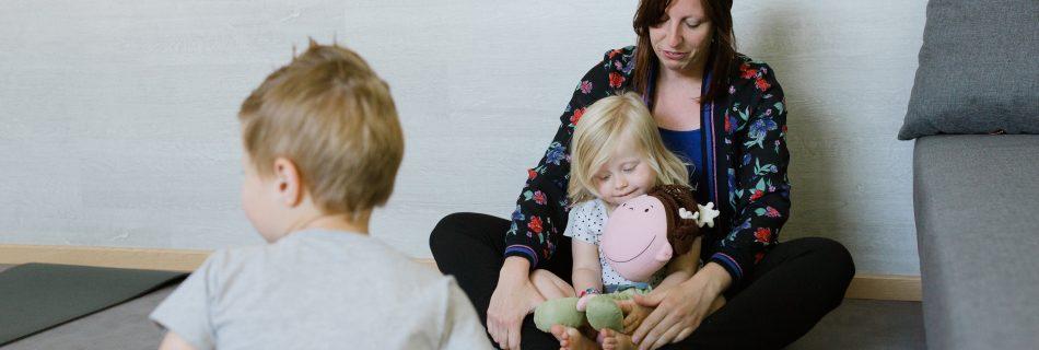 Een mama doet met haar kinderen aan kinderyoga