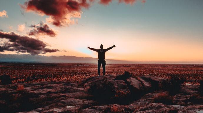 Een man kijkt naar de zonsondergang en is gelukkig