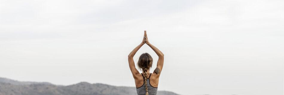 Achterkant van een vrouw die buiten yoga doet