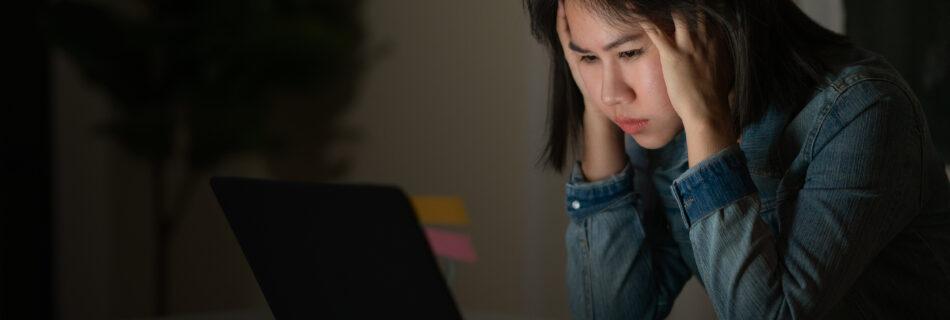 Vrouw zit met een burn-out naar haar scherm te staren