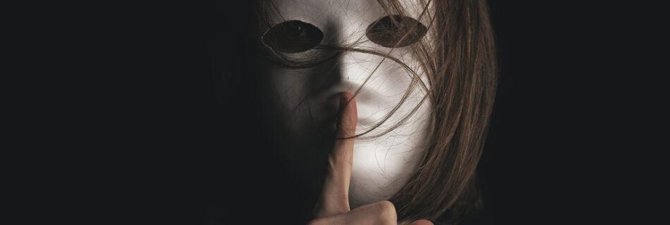 Iemand heeft een masker op en houdt zijn wijsvinger voor de mond om aan te duiden dat je stil moet zijn