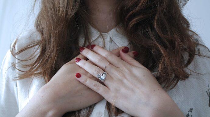 Een vrouw houdt haar handen over haar hart terwijl ze aan hartcoherentie doet